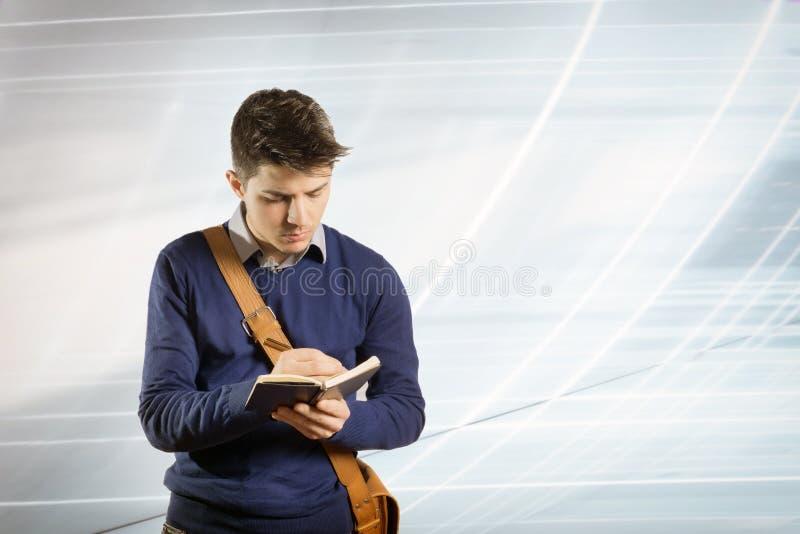 Jeune homme avec l'écriture de chemise et de pull dans un carnet photo stock