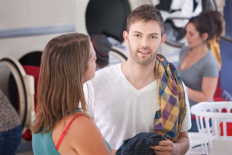Jeune homme avec l'amie dans la laverie automatique photos stock