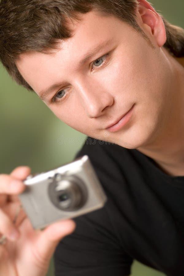 Jeune homme avec l'appareil photo numérique, souriant, à l'extérieur images libres de droits