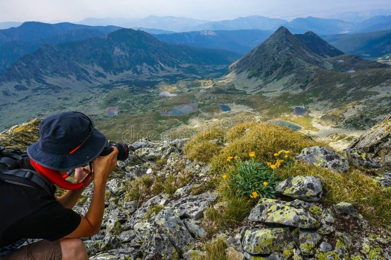 Jeune homme avec l'appareil-photo professionnel photographiant le beau paysage images stock