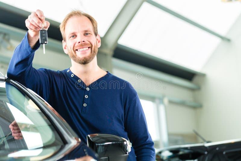 Jeune homme avec l'automobile au concessionnaire automobile images libres de droits