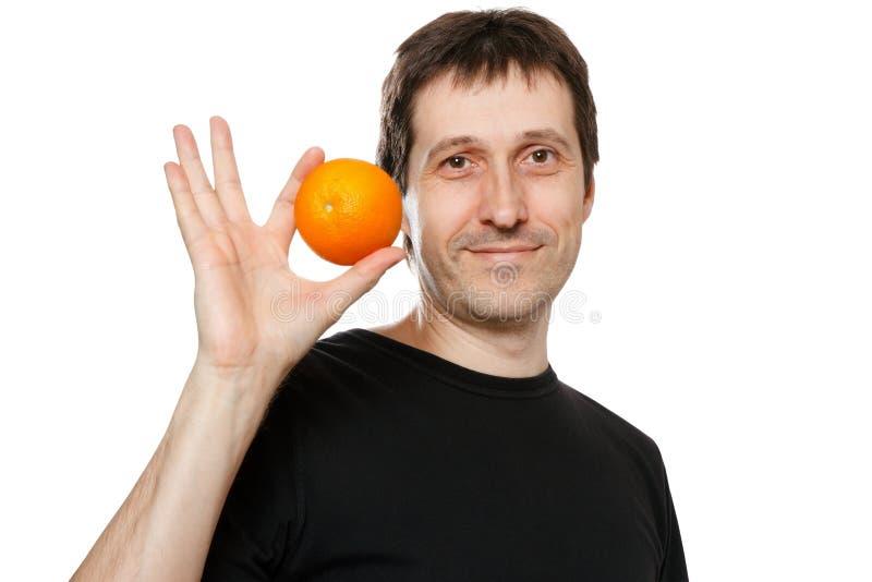 Jeune homme avec l'orange image stock