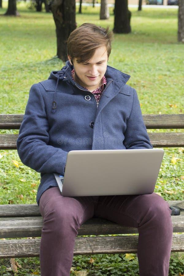 Jeune homme avec l'ordinateur portable en parc photos stock