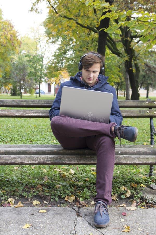 Jeune homme avec l'ordinateur portable en parc images stock