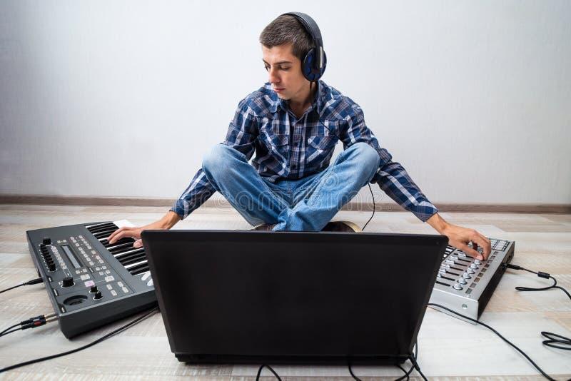 Jeune homme avec l'ordinateur portable et deux synthétiseurs photos libres de droits