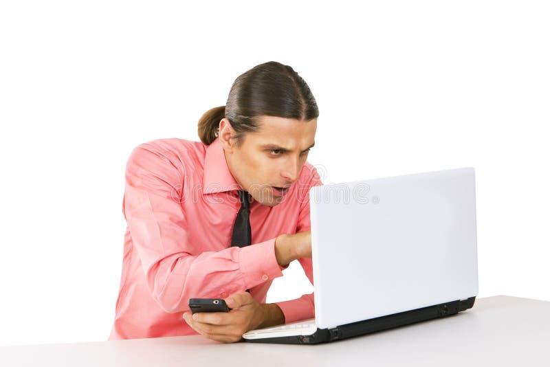 Jeune homme avec l'ordinateur portable regardant le moniteur au-dessus du backgrou blanc photos stock