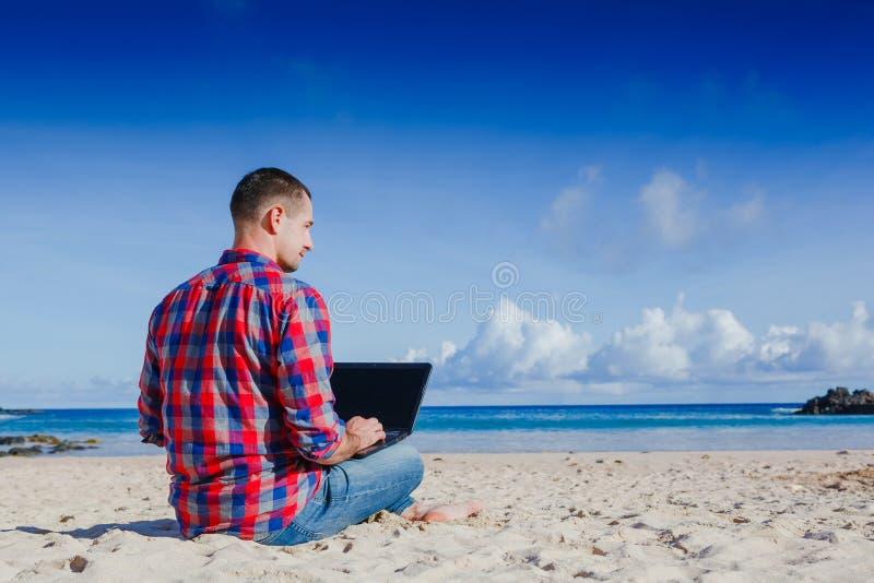 Jeune homme avec l'ordinateur portable travaillant à la plage de sable photos stock
