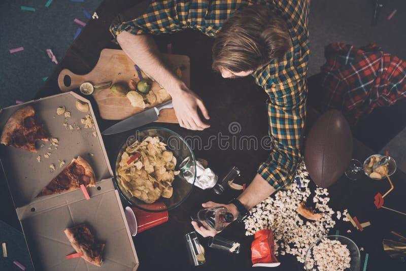 Jeune homme avec la bouteille de whiskey à la table malpropre après partie photos libres de droits