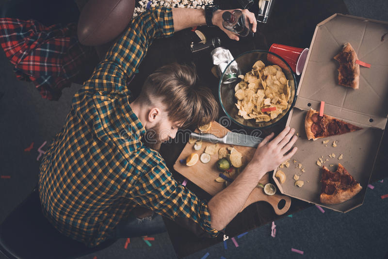 Jeune homme avec la bouteille de whiskey dormant sur la table malpropre images libres de droits