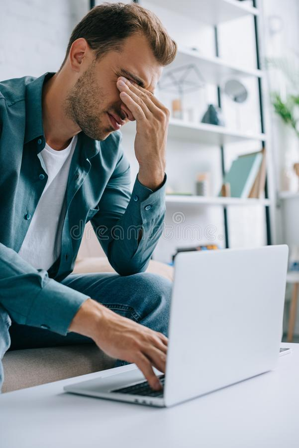 jeune homme avec la douleur dans les yeux et le mal de tête utilisant l'ordinateur portable image stock