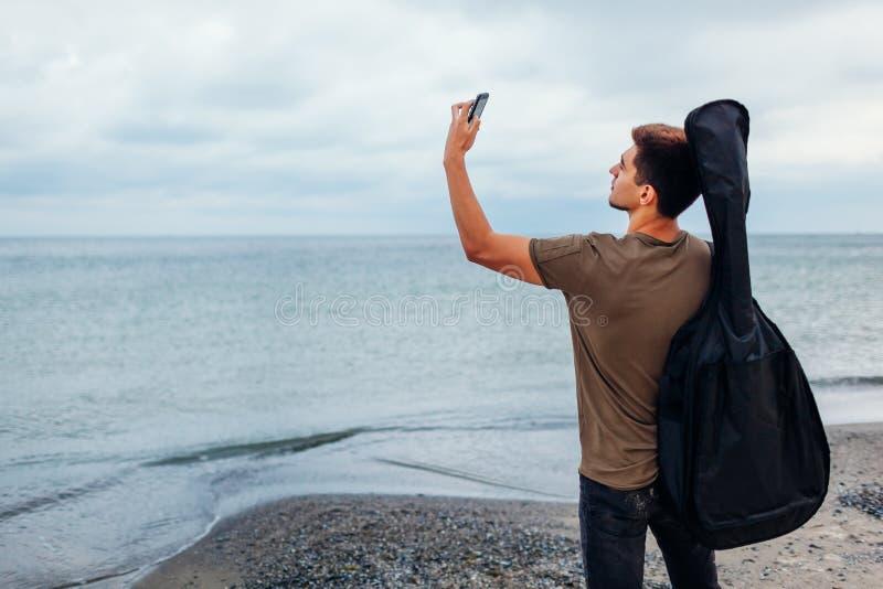 Jeune homme avec la guitare acoustique prenant le selfie utilisant le téléphone sur la plage nuageuse photos libres de droits
