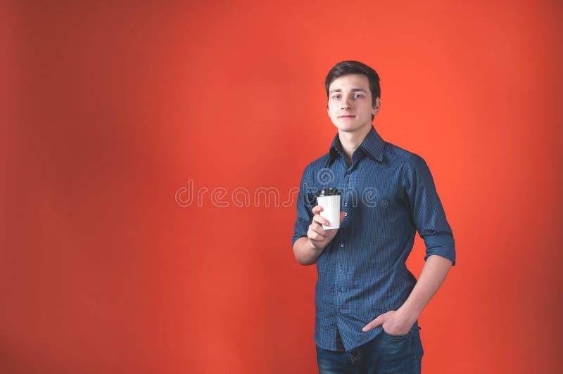 Jeune homme avec la main dans la poche regardant la caméra et tenant la tasse de papier avec du café sur le fond de corail image libre de droits