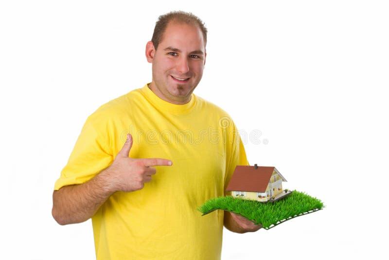 Jeune homme avec la maison modèle image stock