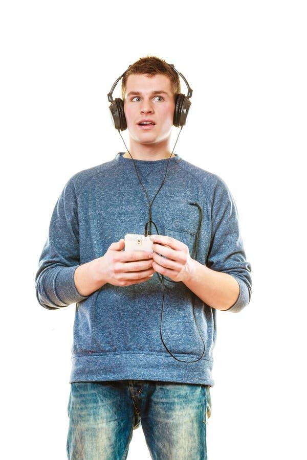 Jeune homme avec la musique de écoute d'écouteurs photos libres de droits