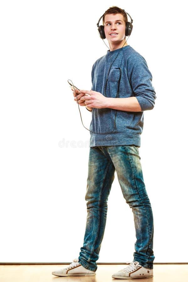 Jeune homme avec la musique de écoute d'écouteurs image libre de droits