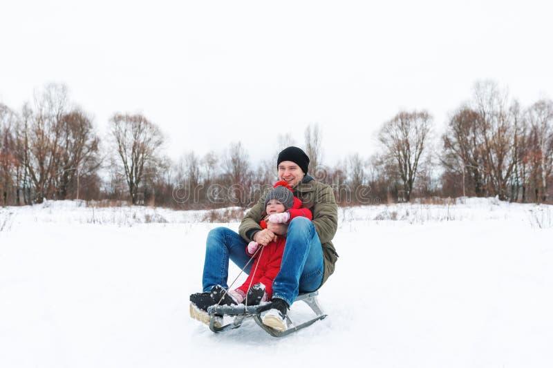 Jeune homme avec la petite fille s'asseyant sur le traîneau dans la neige images libres de droits