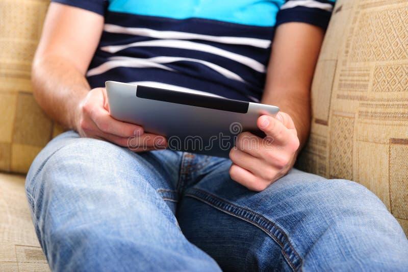 Jeune homme avec la tablette digitale sur le sofa à la maison photographie stock libre de droits