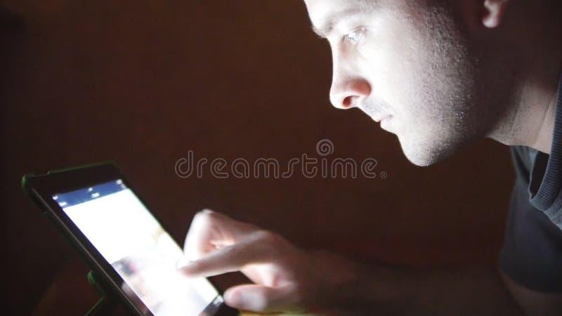 Jeune homme avec la tablette se trouvant sur le sofa Type à l'aide de la tablette à la maison de fin de nuit Rougeoyer léger sur  banque de vidéos