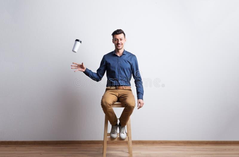 Jeune homme avec la tasse de café de voyage dans un studio se reposant sur un tabouret photographie stock libre de droits