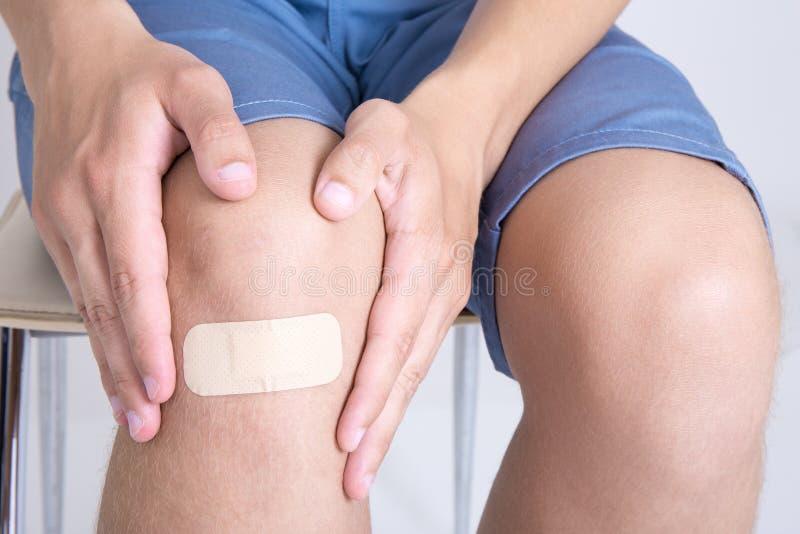 Jeune homme avec le bandage adhésif sur le genou photographie stock