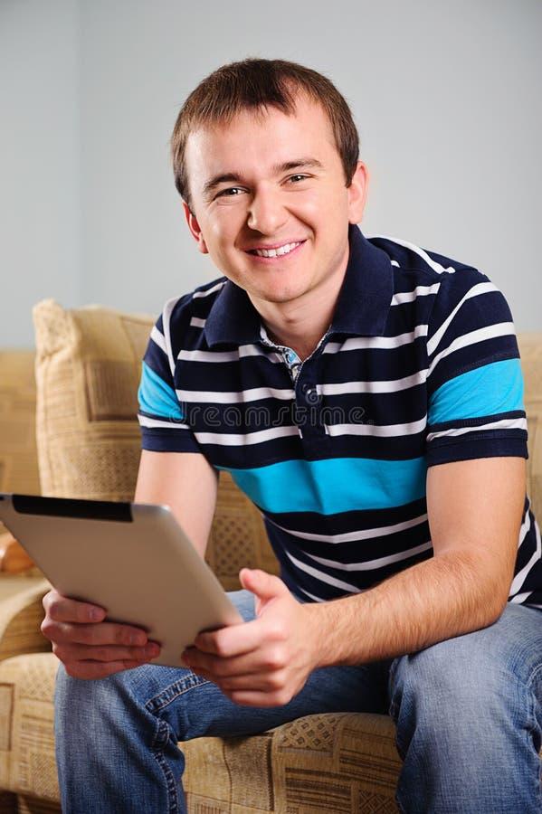 Jeune homme avec le comprimé numérique à la maison photo libre de droits
