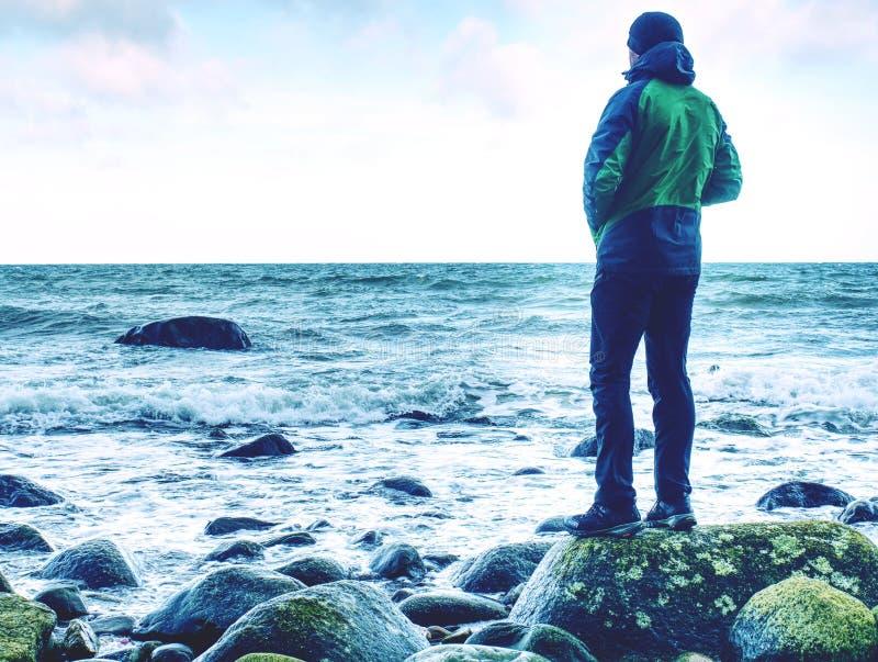 Jeune homme avec le costume touristique regardant sur le paysage marin stupéfiant photo libre de droits