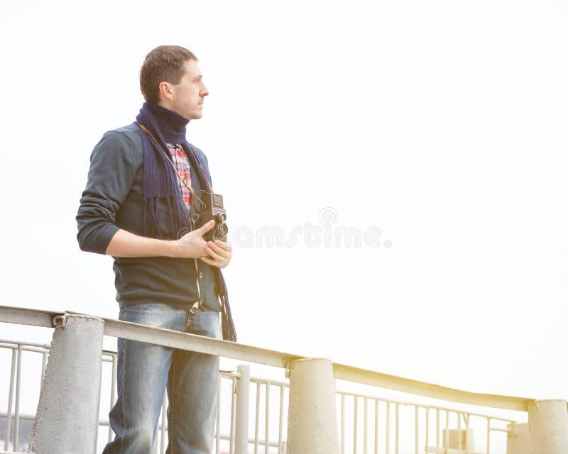 Jeune homme avec le rétro appareil-photo sur une jetée photo libre de droits