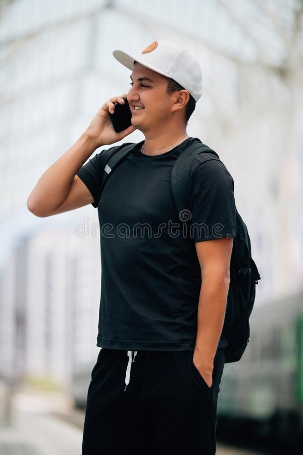 Jeune homme avec le sac à dos à la station de train image stock