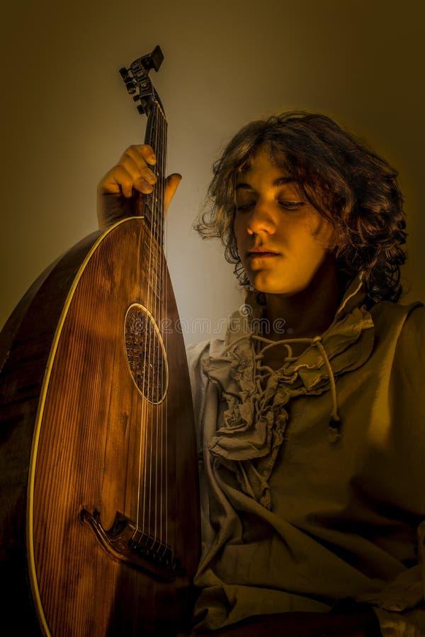 Jeune homme avec le vieux luth de guitare d'Oud image libre de droits