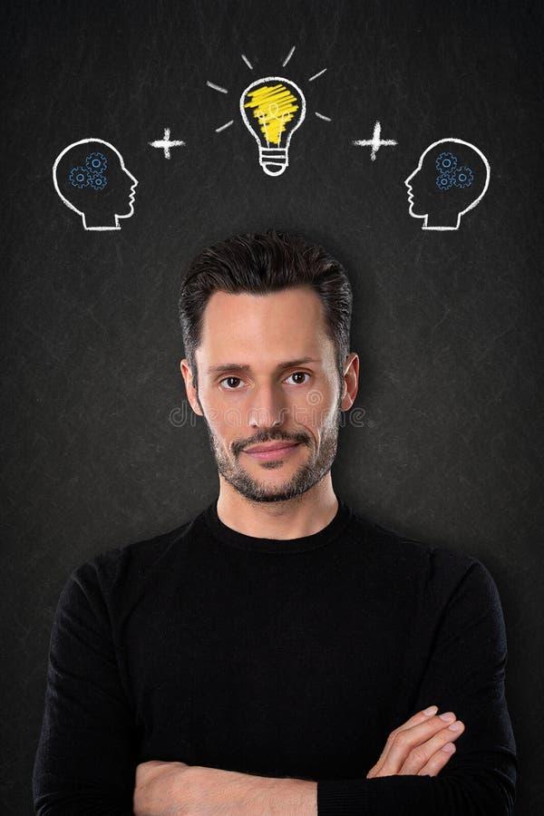 Jeune homme avec les bras croisés, les têtes avec des cerveaux et l'idée d'ampoule sur un fond de tableau noir photos libres de droits