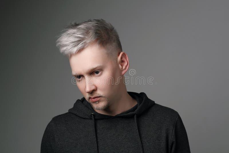 Jeune homme avec les cheveux gris dans des vêtements sport sur le fond blanc et gris Verticale dans le studio Coloration de cheve photo libre de droits