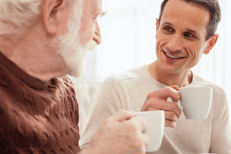 Jeune homme avec plaisir parlant avec son grand-papa photo libre de droits