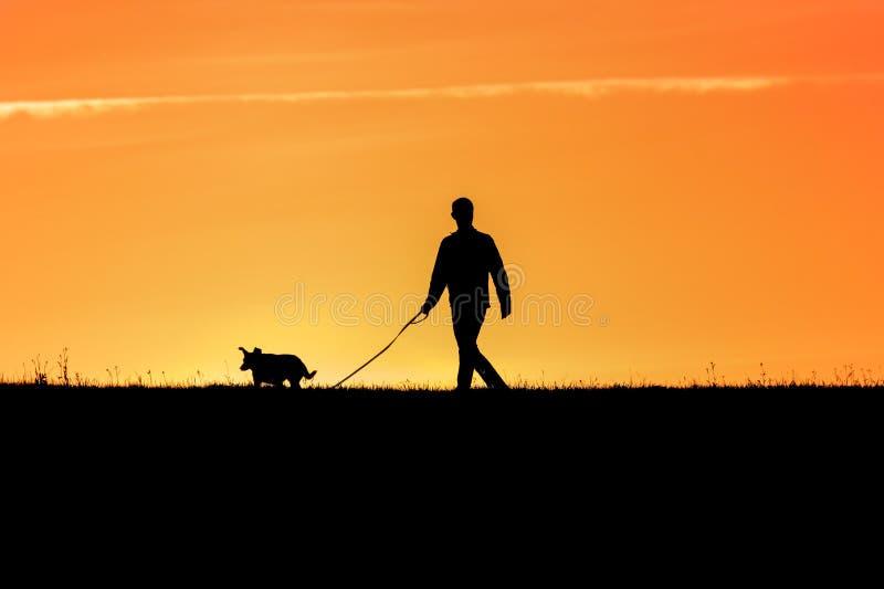 Jeune homme avec son chien - arrière allumé photographie stock