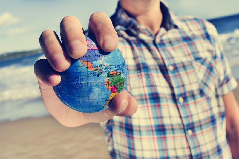 Jeune homme avec un globe du monde dans sa main image stock