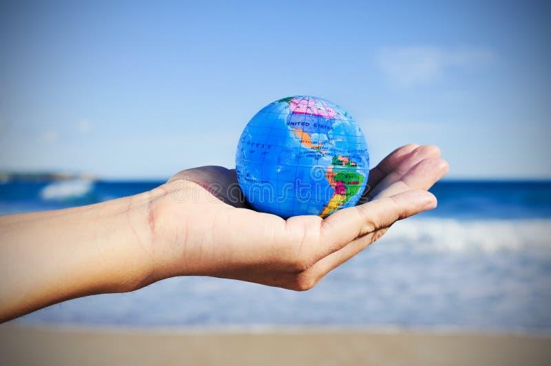 Jeune homme avec un globe du monde dans sa main, vignetted images stock