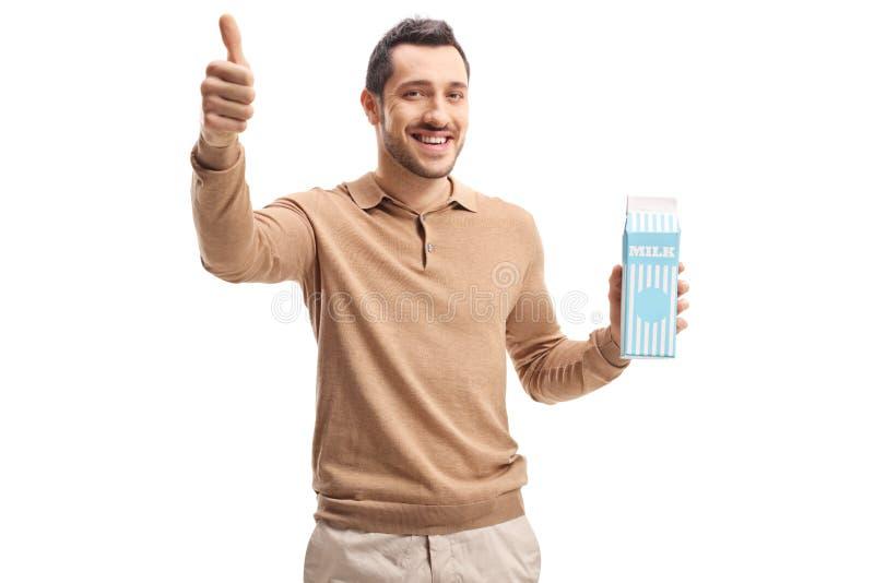 Jeune homme avec un paquet de lait montrant des pouces  photo libre de droits