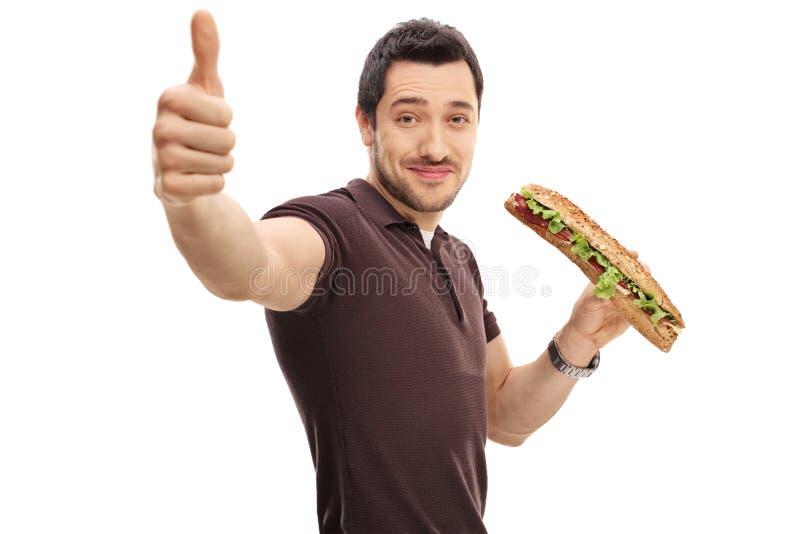 Jeune homme avec un sandwich faisant un pouce vers le haut de signe images stock