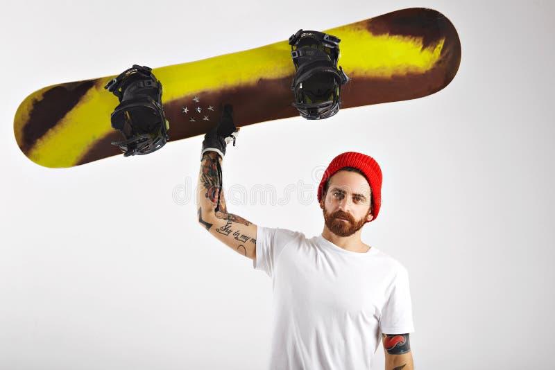 Jeune homme avec un surf des neiges dans le studio photos stock