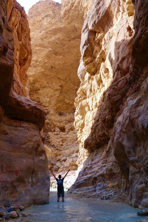 Jeune homme aventureux en ` de Wadi Zarqa Ma en canyon situé dans le paysage montagneux à l'est de la mer morte, près de à Wadi M images libres de droits