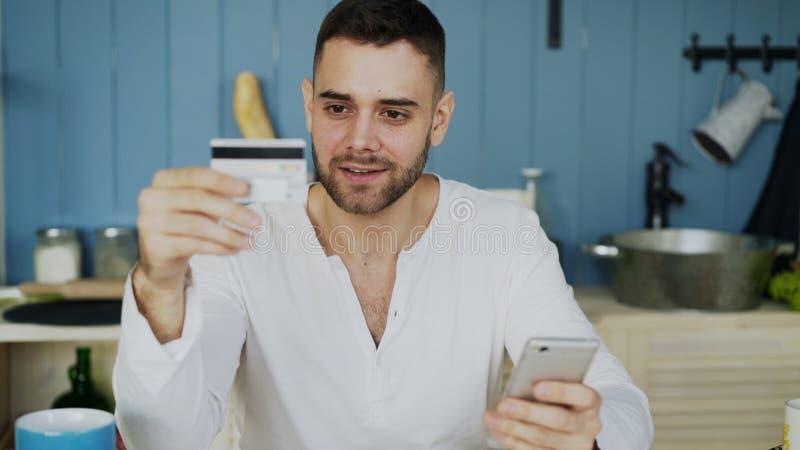 Jeune homme ayant des achats en ligne utilisant la carte de crédit et ordinateur portable tandis que prenez le petit déjeuner dan photographie stock