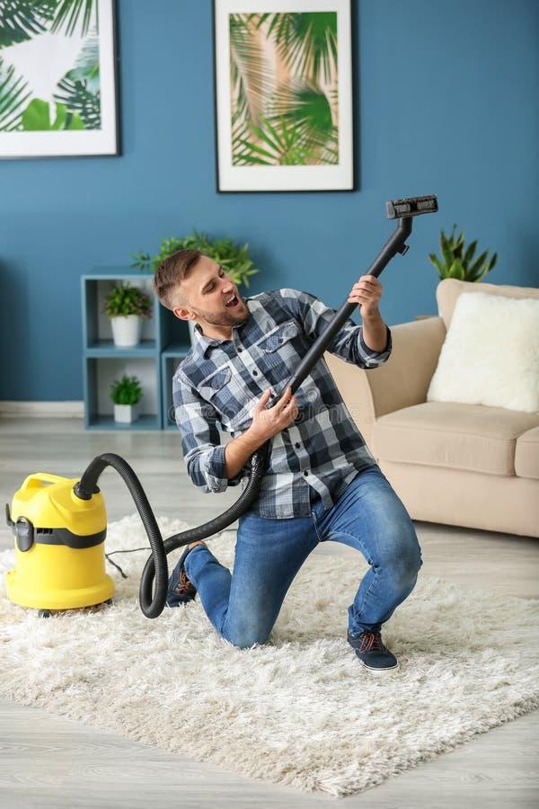 Jeune homme ayant l'amusement avec l'aspirateur tout en enlevant la saleté dans l'appartement images stock