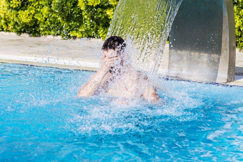 Jeune homme ayant l'amusement avec de l'eau dans la piscine images stock