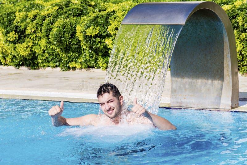 Jeune homme ayant l'amusement avec de l'eau dans la piscine photo stock