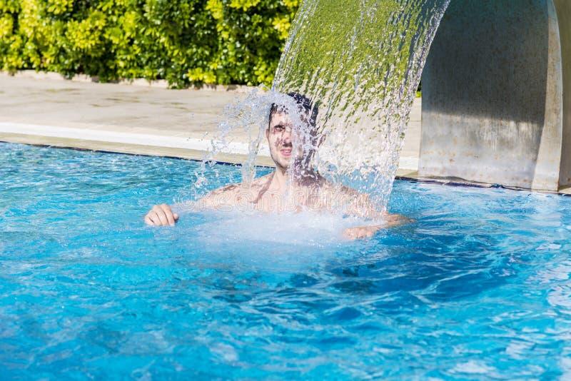 Jeune homme ayant l'amusement avec de l'eau dans la piscine photos libres de droits
