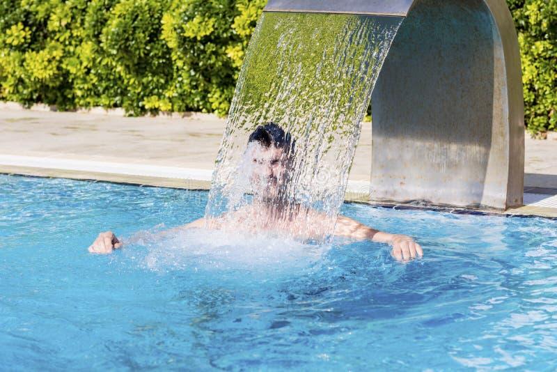 Jeune homme ayant l'amusement avec de l'eau dans la piscine photographie stock