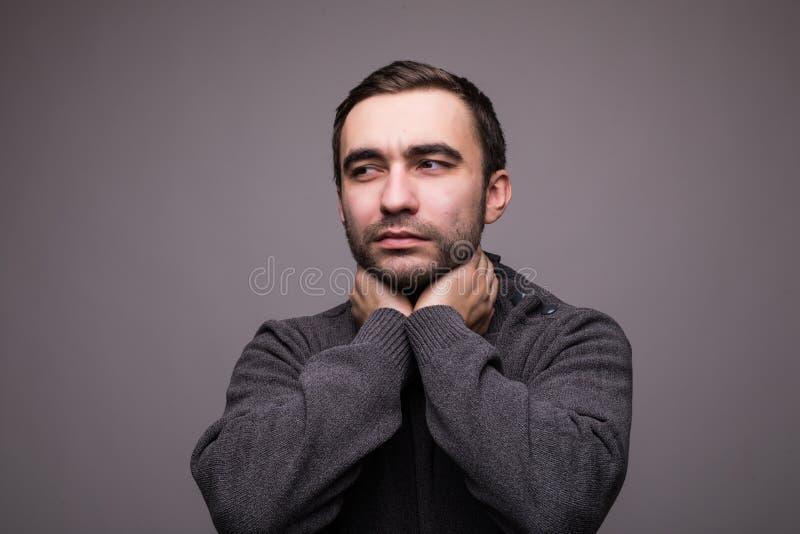 Jeune homme ayant l'angine et touchant son cou sur le fond gris-clair images libres de droits
