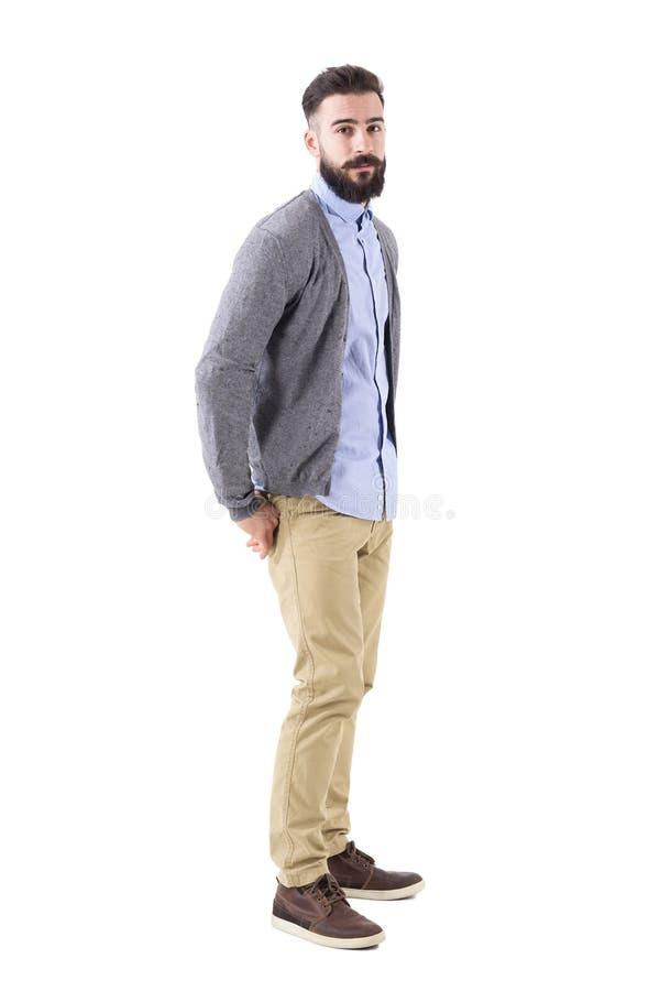 Jeune homme barbu élégant dans le cardigan avec des mains dans des poches arrières regardant l'appareil-photo images libres de droits