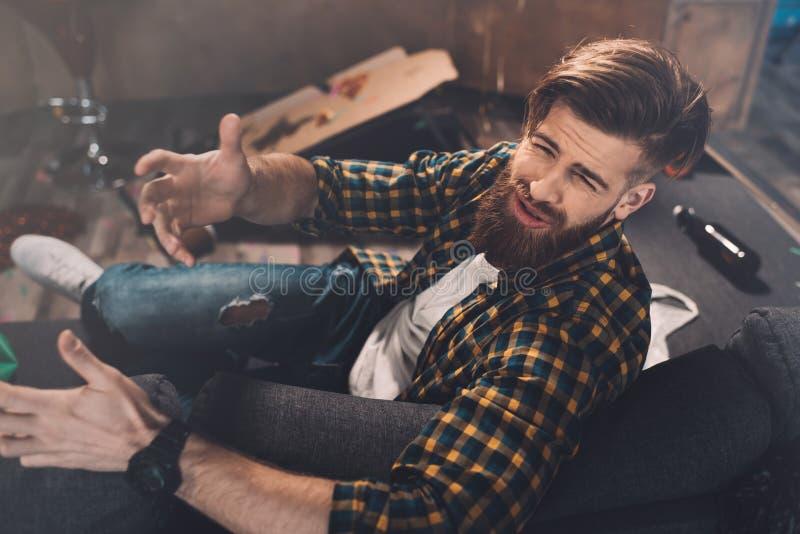 Jeune homme barbu avec la gueule de bois faisant des gestes dans la chambre malpropre après partie image stock