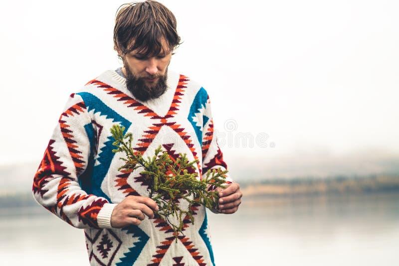 Jeune homme barbu avec le mode de vie de voyage de mode de branche d'arbre de sapin photographie stock libre de droits
