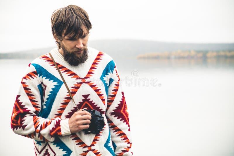Jeune homme barbu avec le rétro mode de vie de voyage de mode d'appareil-photo de photo images stock